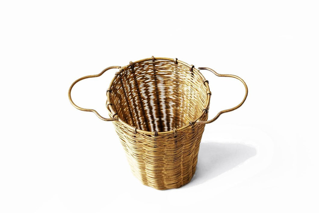 This beautiful and practical tea basket can fit in a mug or tea pot. Due to its depth, you can fill it all the way to the top for a larger pour (for tea pots) or half way for a single dose. Its double handles rest gently on the rim and can be used to brew or strain loose-leaf tea, flowers, and more. Over time, the brass will acquire a rich patina. Hand woven in India.
