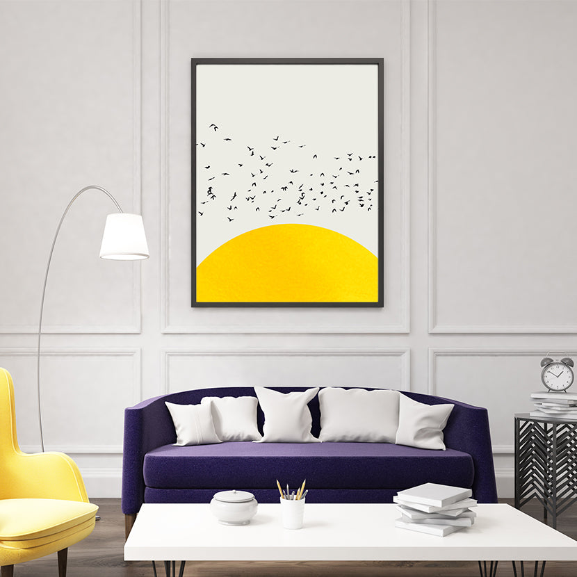 Poster print by Kubistika, with textured yellow sun and black birds, on light grey background, framed in living room