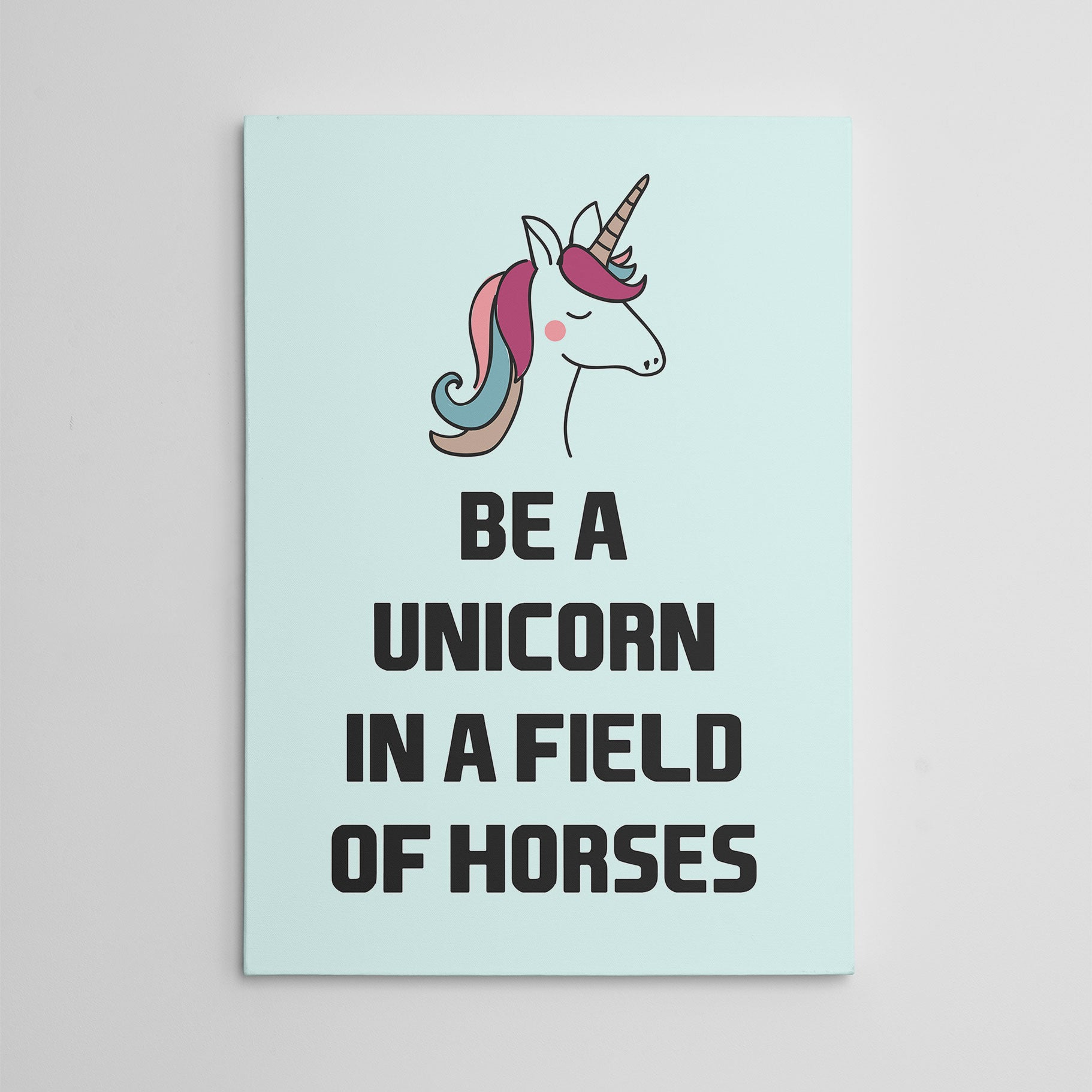 "Canvas print, with black text ""Be a unicorn in a field of horses"" and a colourful unicorn, on light blue background."