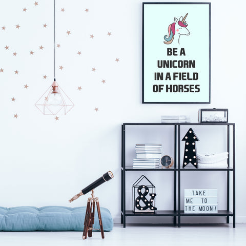 "Poster print, with black text ""Be a unicorn in a field of horses"" and a colourful unicorn, on light blue background - room view"