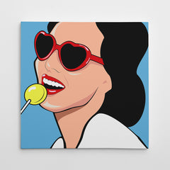 Square pop art canvas print with a girl with yellow candy, red lips and heart sunglasses, on a blue background.