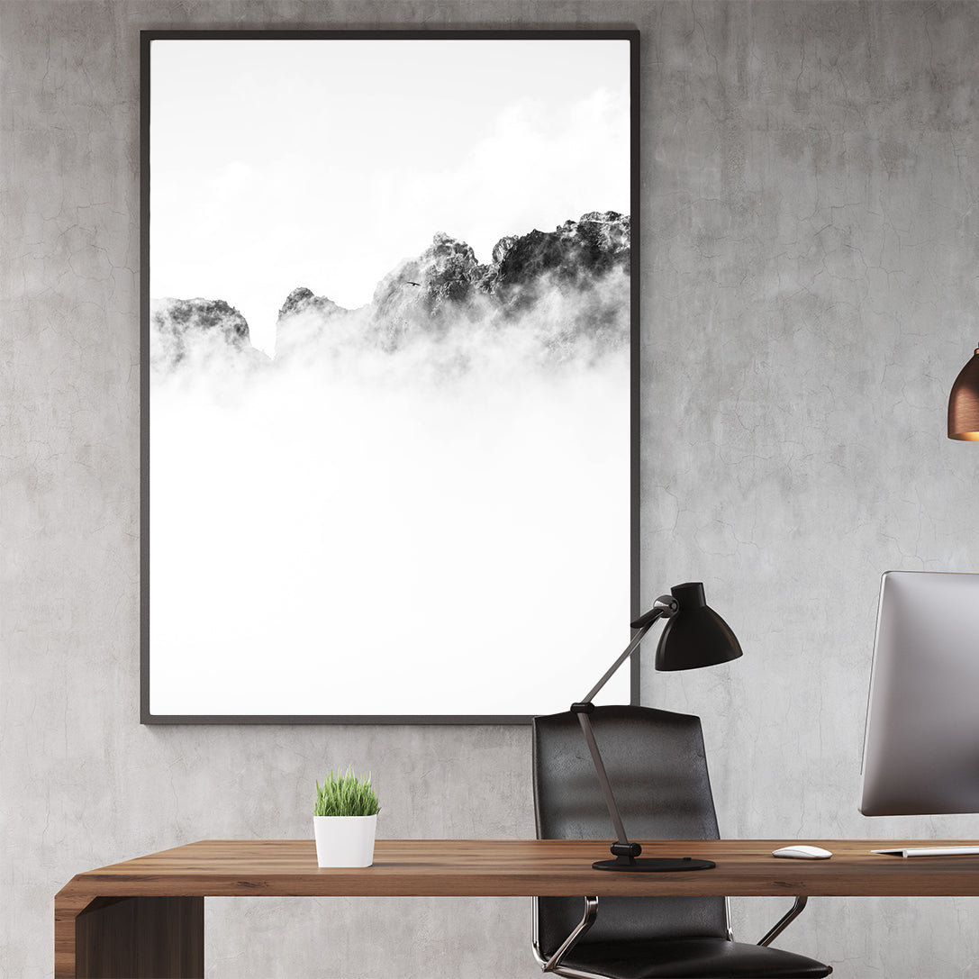 Black and white photo poster print with a bird flying over cloudy mountains, in office