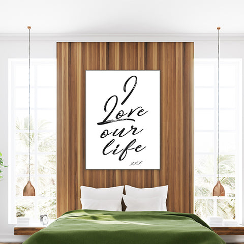 Typography poster print with the quote 'I love our life xxx', on white background; in bedroom