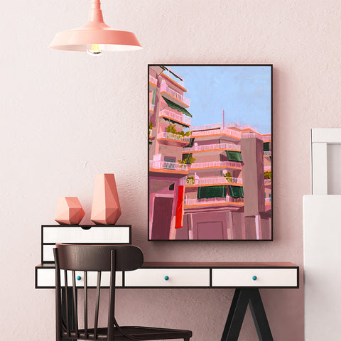 Poster print of an originally painted art by Sophis Novosel, with pink buildings, framed in office