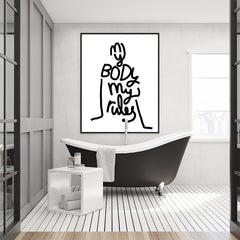 Fashion poster print by Linda Gobeta, with black text ''My body my rules'' written in the shape of a woman, on white background, framed in bathroom