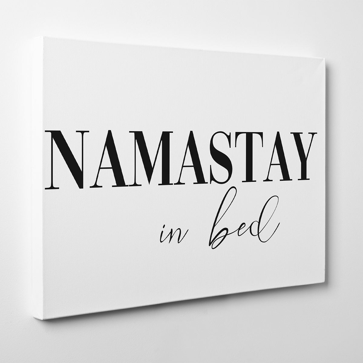 "Canvas print with ""Namastay in bed"" quote, on white background - side view."