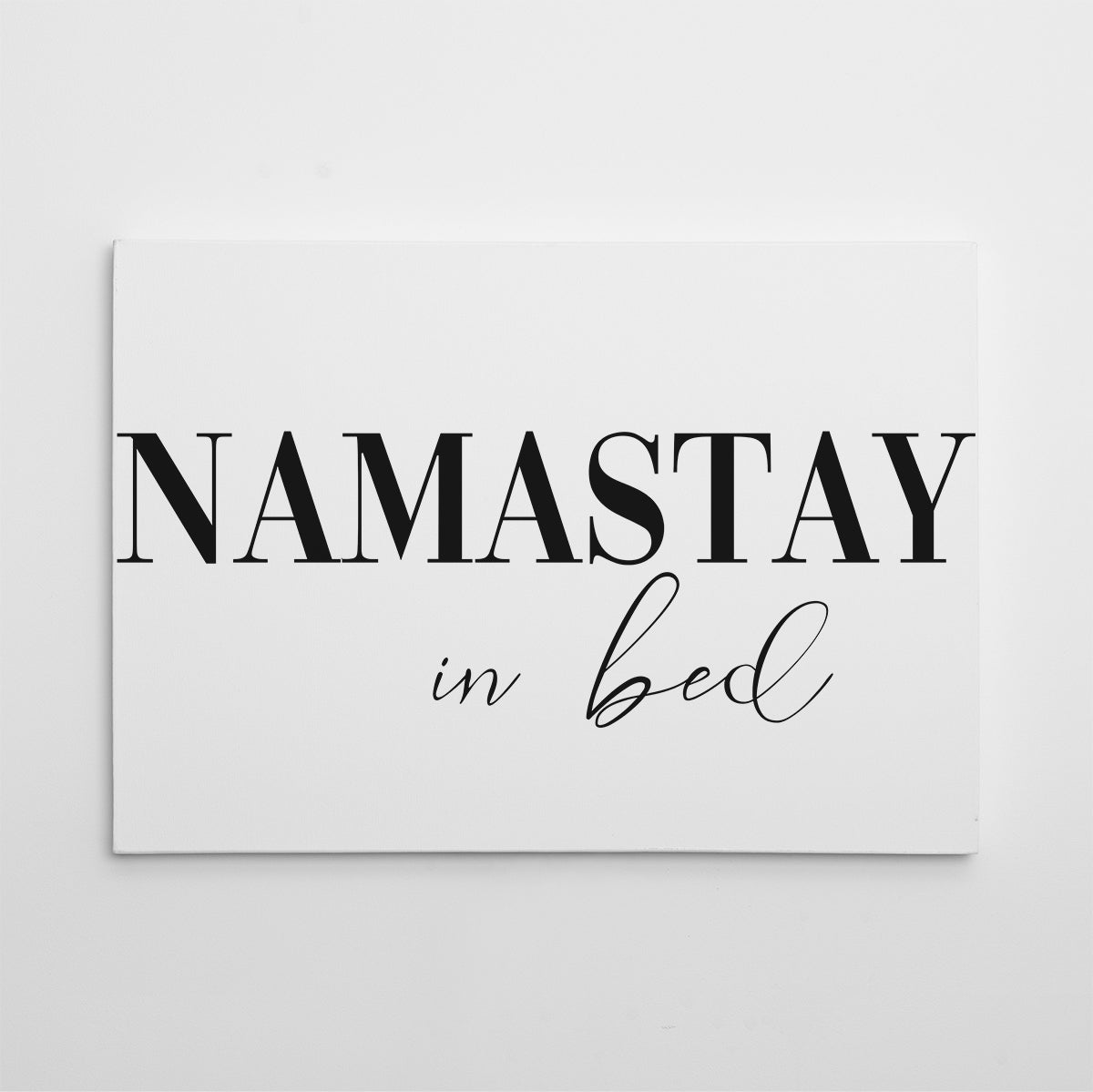 "Canvas print with ""Namastay in bed"" quote, on white background."