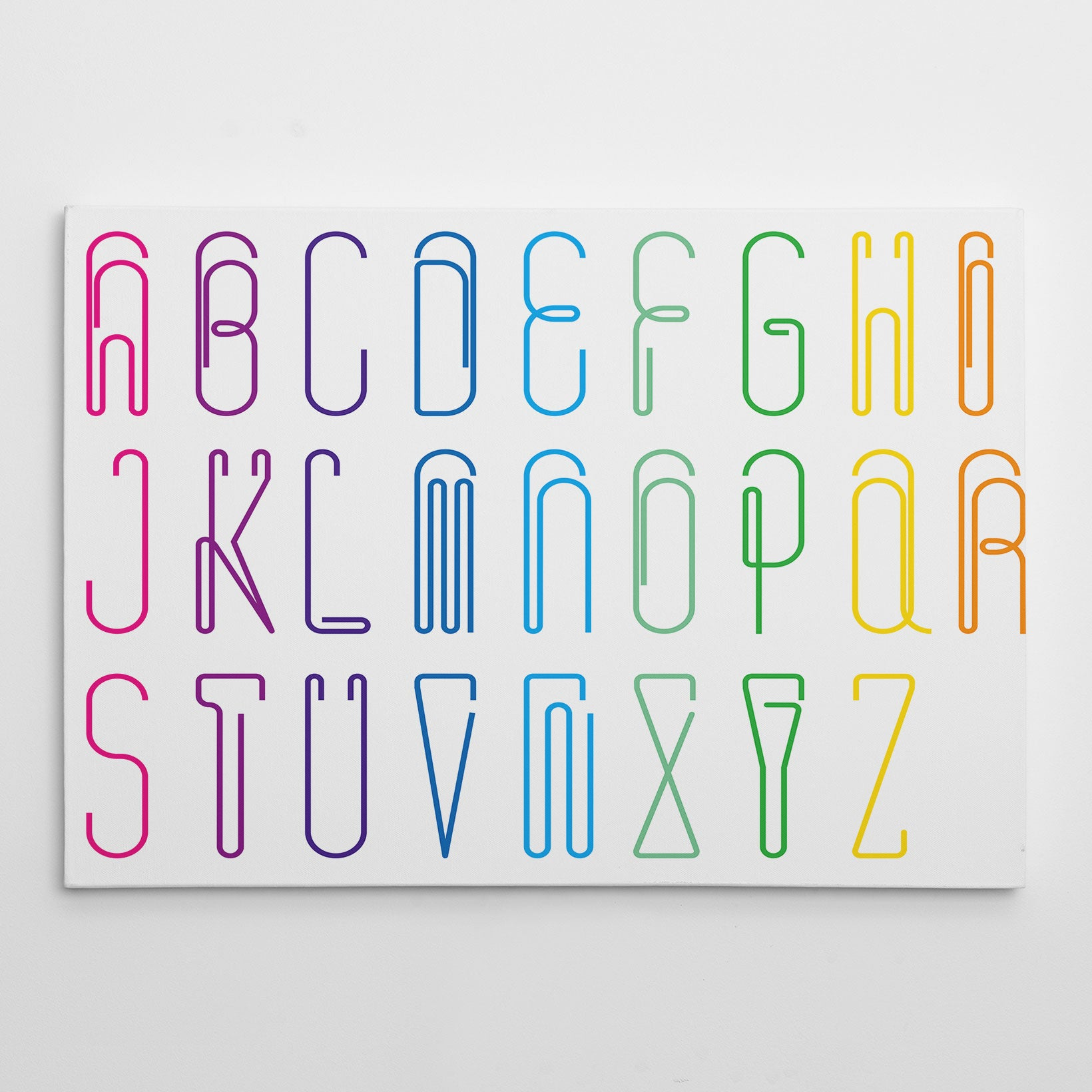 Canvas print with colourful paper clips alphabet letters, on white background.
