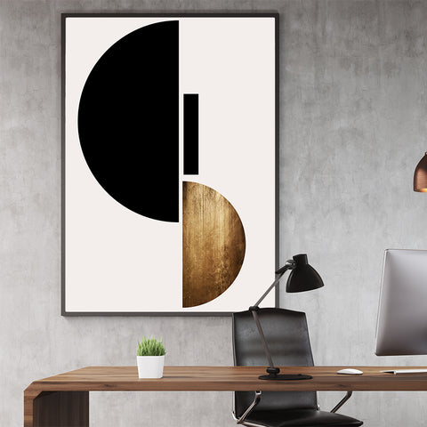 Geometric poster print with black and gold shapes, on light grey background, in office