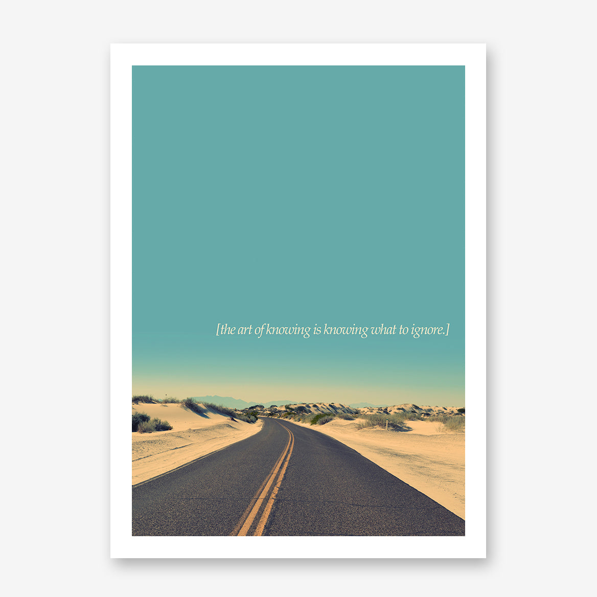 Photography poster print by Kubistika, with a desert road, teal sky and quote 'the art of knowing is knowing what to ignore'.