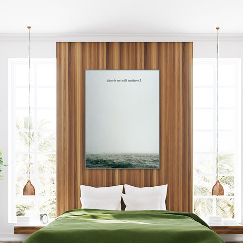 Textured effect photo poster print by Kubistika, with green ocean and quote 'hearts are wild creatures'; in bedroom