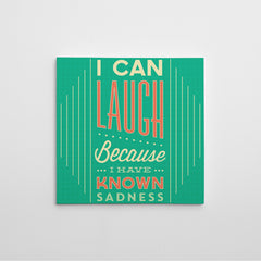 "Inspirational quote canvas print with white and orange text ""I can laugh because I have known sadness"", on teal background."
