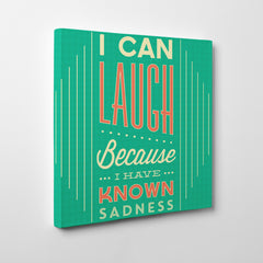 "Inspirational quote canvas print with white and orange text ""I can laugh because I have known sadness"", on teal background - side view"