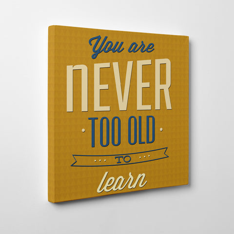 "Retro canvas print with blue and white inspirational quote ""You are never too old to learn"", on a mustard background - side view"