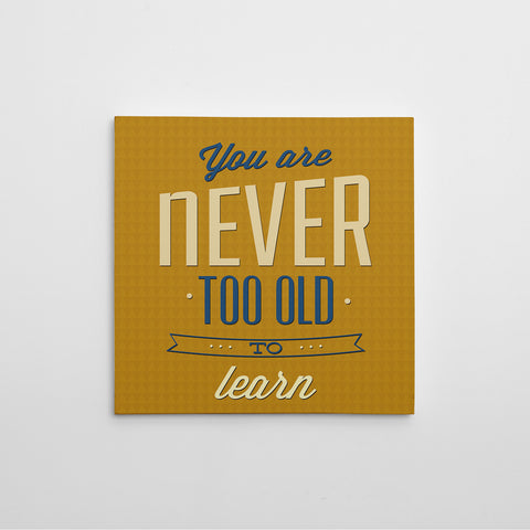 "Retro canvas print with blue and white inspirational quote ""You are never too old to learn"", on a mustard background."