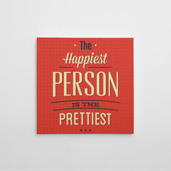 "Canvas print with blue and white text "" The happiest person is the prettiest "" on red background."