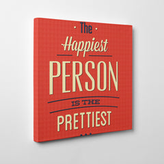 "Canvas print with blue and white text "" The happiest person is the prettiest "" on red background - side view."