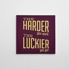 "Canvas print with yellow text ""The harder you work, the luckier you get"" on purple background."