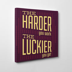 "Canvas print with yellow text ""The harder you work, the luckier you get"" on purple background - side view"