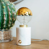 marble and gold exposed bulb table lamp close up