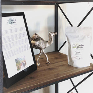 White coffee bag arranged on shelf with metal camel and framed description