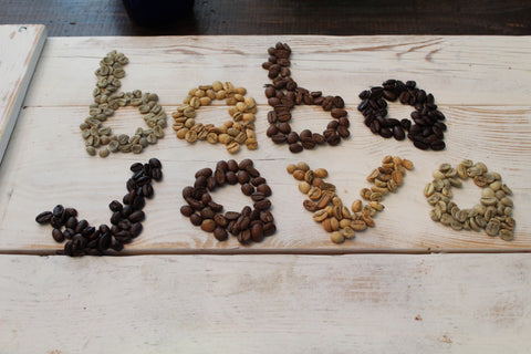 Brown, Yellow, and Green Coffee Beans on White Board Saying Baba Java