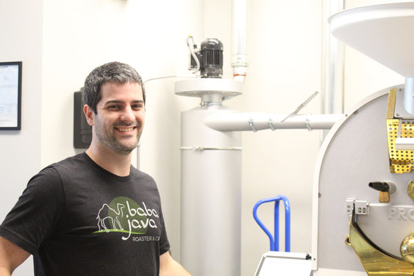 Man wearing a black shirt smiling in front of coffee roaster in a bright room