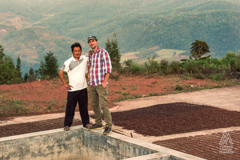 Coffee Farmer and Coffee Mill worker stand side by side with drying coffee