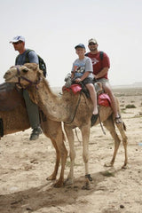 Young boy with dad on a camel in the desert