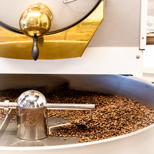 Coffee roaster with coffee beans spinning in cooling pan