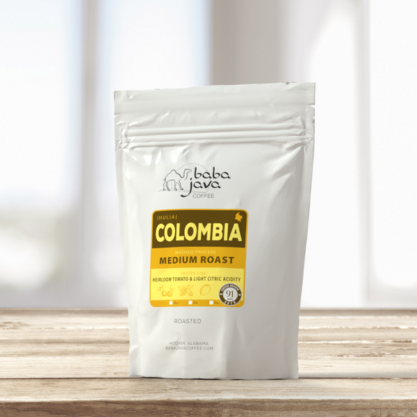 White bag of Baba Java Colombia coffee sits on top of a wooden table with a bright background