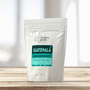 White bag of Baba Java Guatemala Decaf coffee sits on a wooden table with a bright background
