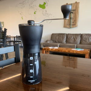 Black hand coffee grinder sitting on a brown table