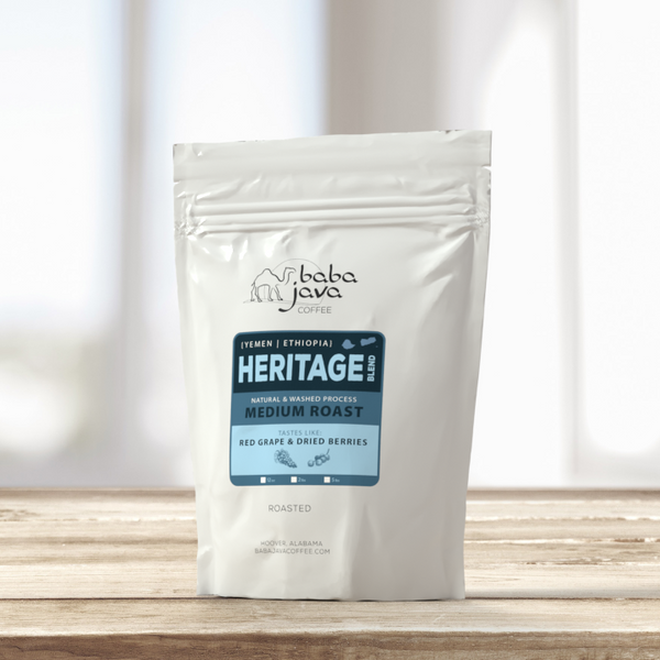 White bag of Baba Java Heritage Blend coffee sits on a wooden table with a bright background