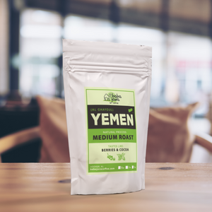 White bag of Baba Java Yemen coffee sits on a wooden table with a bright background