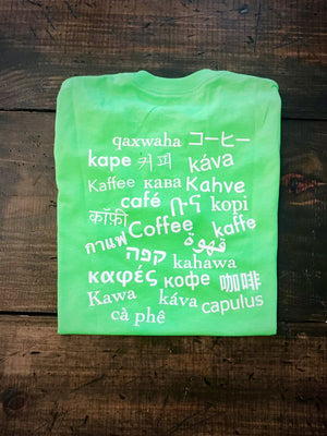 back of green baba java t-shirt on wood background with 'coffee' written in many different languages