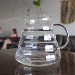 Clear measured Hario coffee server on a brown table