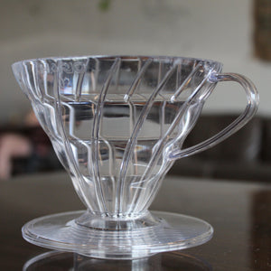 Clear v60 coffee dripper sitting on a brown table
