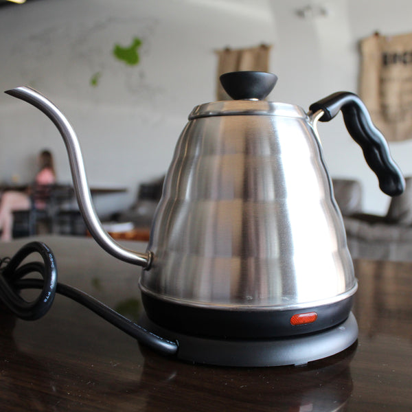 Silver and black electric coffee kettle sitting on a brown table