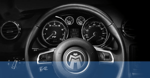 Black and white photo of car steering wheel with Module Master logo over it and dashboard instrument panel.