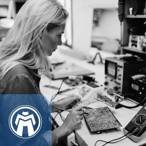 Black and white photo of blond woman working on circuit board.
