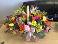 Rainbow colurs basket created in a variety of seasonal flowers , florist choice. Size in picture is medium