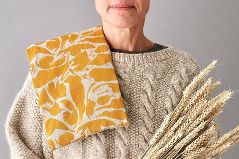 woman using wheat packs for back pain