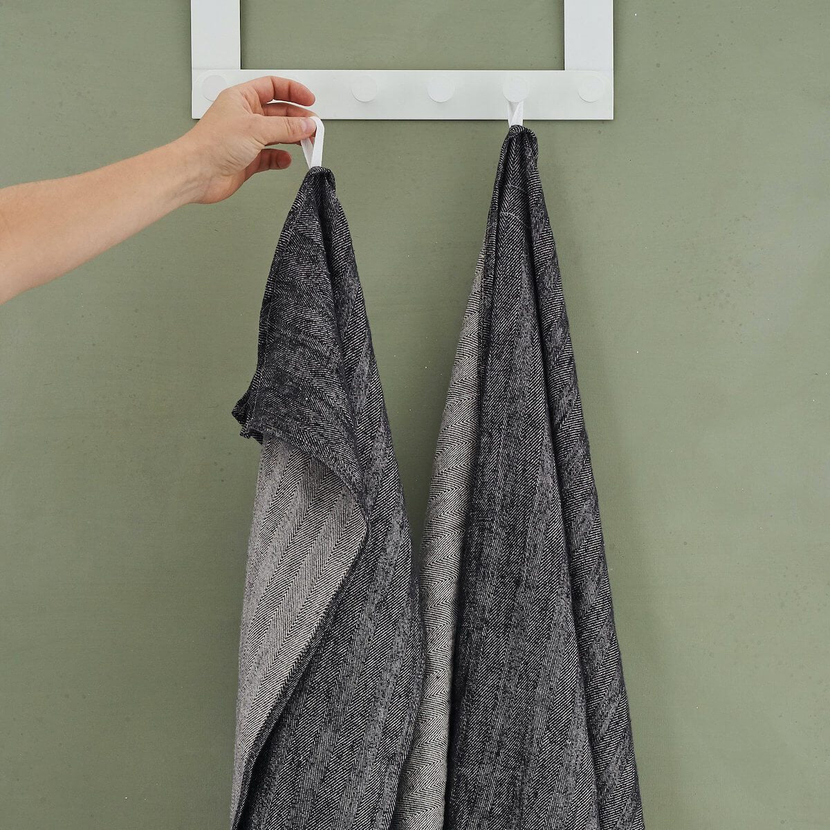 linen hand towels being hung on wall