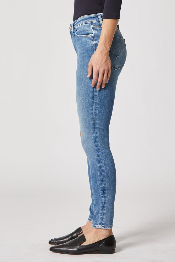 Load image into Gallery viewer, SIDE VIEW of the Nico Mid-Rise Super Skinny Ankle Jean by HUDSON jeans. Designer pants worth their weight in gold. These bottoms last A LIFETIME (relatively speaking). In this snapshot we can see a clean hem-job and slight striping detail along the seams due to the unique wash of denim (dye-job called Remixing). This pair of denim is paired wth black loafer shoes and a black quarter sleeve top. White background. Stock photo from Hudsonjeans.com