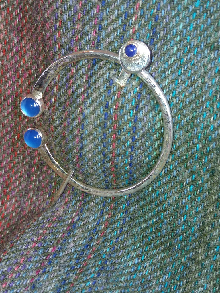Silver cloak pin with blue stones