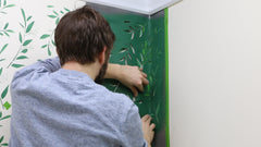 Push the stencil template into the corner of the wall