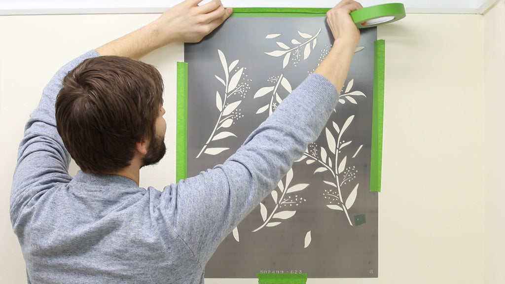 Press the stencil to the wall and mask the edges with Frog Tape Painters Tape