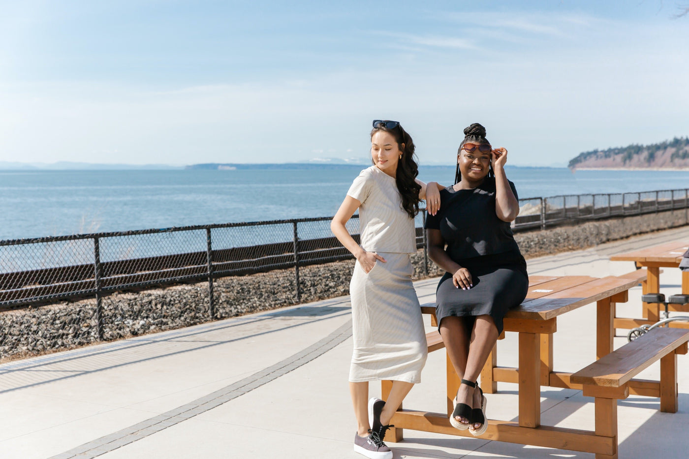 two ladies wearing smash + tess t-shirt and skirt sets sat on table next to the ocean
