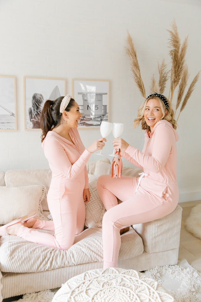 two women in living room with glasses of wine and pink jillian harris rompers